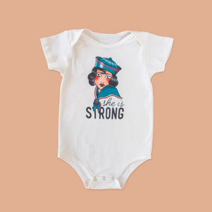 product photo of the she is strong onesie
