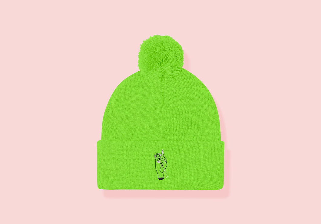 Neon green cuffed beanie with pom. Embroidered hand holding a dart in black and white