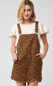 Leopard print pinafore dress featuring raw hem detail. Pockets at side and back. Adjustable straps.
