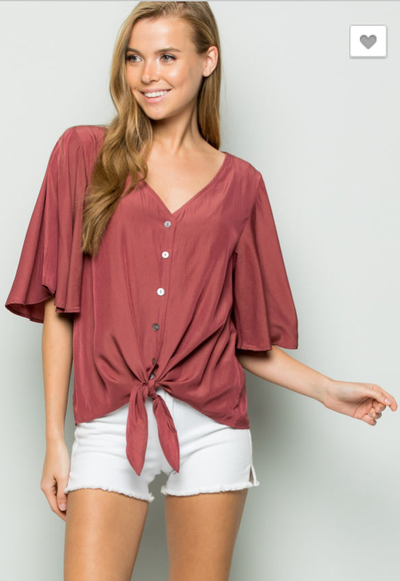 A woven shirt top featuring a V-neckline and button down with self-tie hem