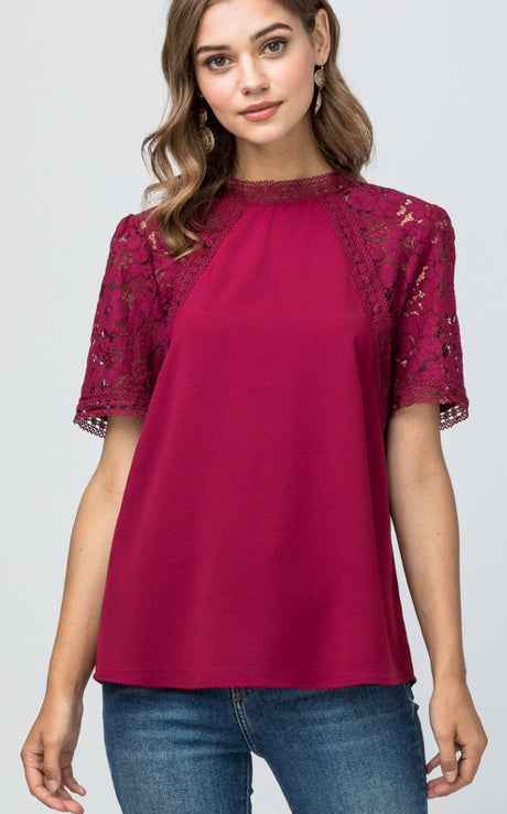 Mock-neck top featuring lace detail at sleeve. Keyhole button closure at back