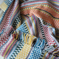 Close up showing wide variety of colours on the check and striped recycled plastic bottle throw-blanket.
