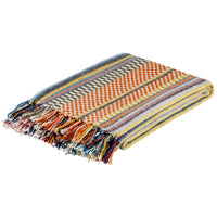 Folded multicoloured blanket of checks and stripes, including reds, yellows and oranges. With fringe. Sustainable made from recycled plastic bottles.