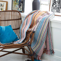Eco-friendly recycled plastic bottle blanket.  Check and striped multicoloured design, including red, yellow, white and blue.  Placed beside a wooden chair.