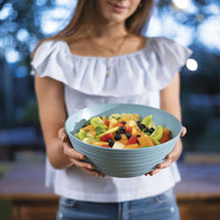 Large sky blue salad bowl with blue lid, by Guzzini.  It has a ribbed, organic texture, inspired by nature.  In the image it is held by a female and contains fruit salad.