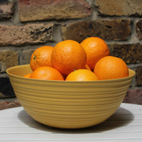 Large ribbed yellow bowl, made from recycled plastic.  Full of oranges.
