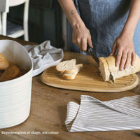 Demonstration of bread being cut on the reverse side of the bread bin lid. The lid is bamboo, the bin is recycled plastic (bottles) in off-white colourway.