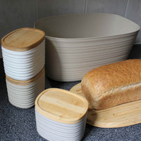 Guzzini bread bin. Rippled, off-white recycled plastic bread bin with bamboo lid, upon which is a loaf of wholemeal bread.