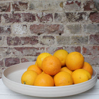 Stack of oranges in an oval shaped fruit bowl made from eco-friendly recycled plastic.  A brick wall is in the background.