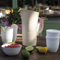 Water or cocktail pitcher and lid made from recycled plastic bottles.  The lower half of the jug has a ribbed, pottery wheel style finish in off-white.  It is on a table, beside tumblers, limes and lemons.
