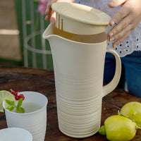 Water or cocktail pitcher and lid made from recycled plastic bottles.  The lower half of the jug has a ribbed, pottery wheel style finish in off-white.  The slatted lid spout is shown.