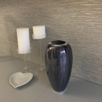 Eco friendly, contemporary, recycled aluminium brushed silver and black vase, similar in shape to the gherkin building in London, with the top chopped off.  On display next to two candle sticks