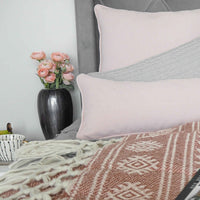 Bedroom scene of recycled home decor with pink and grey cushions.  To the left is a brushed grey recycled aluminium vase with peach roses.