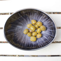 Recycled metal oval bowl with brushed grey/silver starburst design and varnished finish.  Contains a small selection of olives.