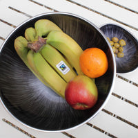 Round recycled metal bowl with brushed grey starburst design.  In the bowl is fruit, including bananas label with the Fairtrade Foundation.