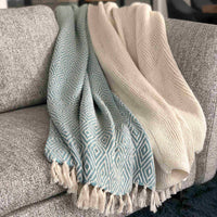 Two ReChic recycled throws-blankets on a grey sofa. One is sky blue with a diamond geometric design. The other is cream and knitted.