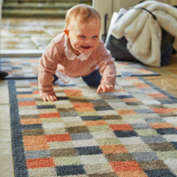 Baby crawling on a recycled cotton hallway mat.  It has a check design with reds, terracotta and blues.