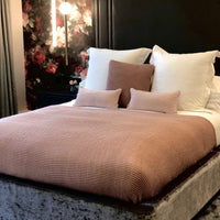 Double bed dressed with ReChic pink and mauve recycled plastic bottle knitted layering.  Eco-friendly, luxury home decor.