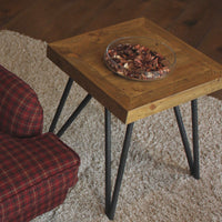 Contemporary recycled furniture. Reclaimed pallet wood lamp table with black metal legs and a bowl of pot pourri resting on it. Sitting on a beige shaggy rug.