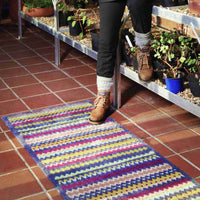 Close up of recycled cotton doormat with zig zag stripes. Multi coloured, including, grey, purple and lime green. A person has one foot on the UK made rug.