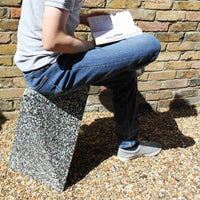 Recycled plastic Ecopixel grey Delta outdoor stool with a man sitting on top of it reading a book.