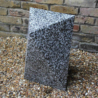 Asymmetrical triangular prism recycled plastic stool or side table. Dark grey, black and white pixels creating a terrazzo like effect. Displayed on gravel in front of brick wall.  Outdoor furniture By Ecopixel.
