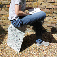 Recycled plastic Ecopixel white Delta outdoor stool with a man sitting on top reading a book.