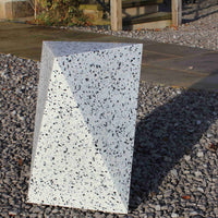Terrazzo-like geometric stool on gravel. Optical illusion makes it look like it's balancing on one edge. A long shadow is cast in the background. Furniture by Ecopixel.