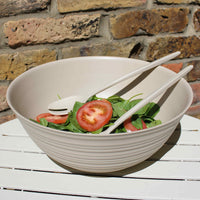 Off-white recycled PET (plastic bottles) bowl, with ribbed, organic looking exterior.  Containing matching salad servers and a tomato and spinach salad.