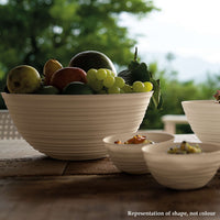 Three Guzzini Tierra, recycled plastic white bowls of varying sizes.  They have a ribbed, organic exterior and each is full of fruit.
