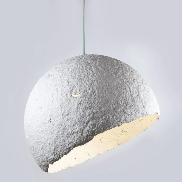 Environmentally friendly, white, half moon pendant lamp.  Made with paper mache (papier-mâché), it has an organic, rough textured finish textured finish and a pale blue cable.  Set against a grey background.