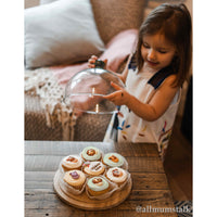 Toddler lifting the recycled glass dome from an FSC wooden board displaying a selection of cupcakes.