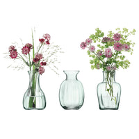 Three recycled glass vases, two of which contain a posy of flowers.  Part of the mouthblown Mia range, by LSA.