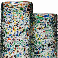 Close up of two sustainable recycled glass vases by La Galeria.  The Barcelona Rainbow vase is clear and covered with multi coloured decorative droplets, to give it a modern, contemporary look.