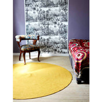 Recycled sustainable cotton round yellow rug on wooden floorboards.  Beside is bohemian looking furniture and decor with vibrant patterns.  Goodweave certification ensures the rug is ethical.