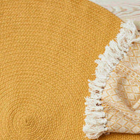 Birds-eye view of round yellow eco rug made from recycled cotton. Beside is a yellow throw.