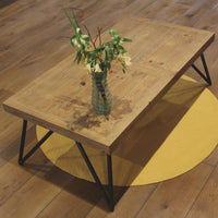 Reclaimed pallet wood coffee table with round mustard yellow recycled eco rug and glass vase.  Ethical home decor.