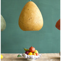 Yellow ochre eco friendly pendant lamp hanging artistically above a bowl of fruit.  Egg-shaped (with the bottom removed) and smooth paper mache (papier-mâché) textured finish.