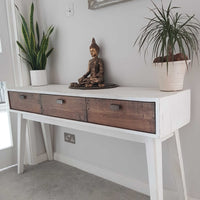 White eco-friendly reclaimed wood console table with drawers. At either end are plants and at the centre is a Buddha statue.
