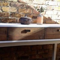 Reclaimed wood white console table with three drawers.  On top is a recycled glass bottle vase.