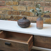 Recycled white wood console table with one of the drawers open on display.  Behind the table is a brick wall.