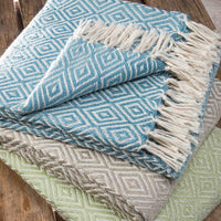 Three folded throws in sky blue, stone grey and mint green. Each has a small white diamond geometric pattern and white fringe. Made from environmentally friendly recycled plastic bottles.