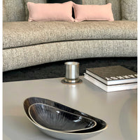 Contemporary grey room, with recycled pink cushions on a grey sofa and aluminum bowls in the foreground.