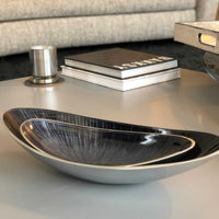 Two oval bowls, one resting inside the other.  Recycled aluminium with a varnished, brushed grey starburst design.