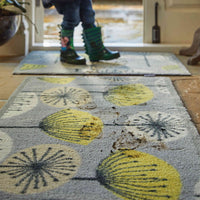 Muddy footprints on a grey recycled cotton eco doormat, with graphic flowers on it, that look like dandelions.  Made in the UK.
