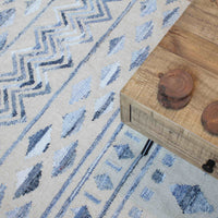 Corner of a reclaimed wood coffee table sat upon an ivory-coloured wool rug with tribal pattern made from recycled denim.  Eco friendly and sustainable home decor.
