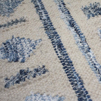 Close up of an ivory coloured wool eco rug, with a diamond pattern made from recycled denim. Ethically sourced.