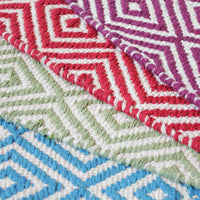 Selection of four geometric rugs made from recycled cotton.  From bottom to top they are turquoise blue, green, red and purple.