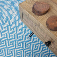 Reclaimed wood coffee table on top of a turquoise blue recycled rug made from cotton.  The rug has a diamond geometric pattern and is ethically sourced.