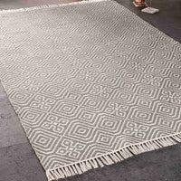 Stone grey kilim rug 120 x 180cm with geometric pattern. White fringe at both ends. Beside it is a bottle of wine and glass. Made from eco-friendly recycled plastic (P.E.T.) bottles.